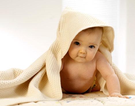 f5a269429d2307 Baby mit Stofftier trägt Kapuzenwickeltuch aus Bio Waffelpikee in Naturfarbe  nach dem Baden